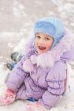 O assento de cinco anos engraçado da menina rolou para baixo uma corrediça do gelo Fotos de Stock Royalty Free