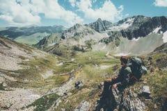 O assento de relaxamento do viajante do homem apreciando montanhas ajardina a caminhada do estilo de vida do curso Imagens de Stock