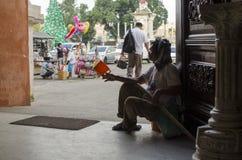O assento do homem cego, implora no portal da porta da jarda da igreja para procurar a esmola silhuetas fotografia de stock