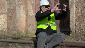 O assento do inspetor de construção e toma a imagem no telefone esperto video estoque