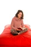 O assento e a leitura da jovem mulher um livro no quadrado vermelho deram forma ao feijão fotografia de stock royalty free