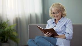O assento fêmea consideravelmente maduro no auto-desenvolvimento do sofá e da leitura registra, passatempo video estoque