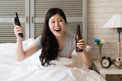O assento fêmea na cama mantém-se rir fotos de stock royalty free