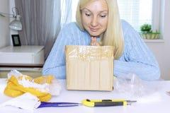 O assento louro entusiasmado e a abertura da mulher uma caixa, um pacote, objetos na tabela estão na confusão imagens de stock