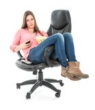 O assento preguiçoso da mulher esticou para fora em uma poltrona com pipoca e uma bebida Fotografia de Stock