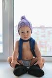 O assento só do bebê adorável do bebê de um ano na soleira weared no chapéu, nas sapatas e no lenço do inverno, dentro fotografia de stock royalty free