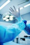 O assistente ajuda o cirurgião posto sobre luvas do látex Imagens de Stock Royalty Free