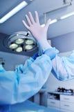 O assistente ajuda o cirurgião posto sobre luvas do látex Foto de Stock