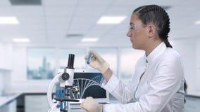 O assistente de laboratório fêmea conduz análises laboratoriais de um líquido azul em um tubo de ensaio Laborat?rio cient?fico Mo filme