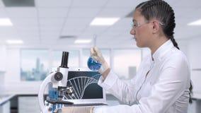 O assistente de laboratório fêmea examina uma cura para o câncer r Movimento lento video estoque