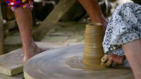 O assistente gerencie a roda pelo vaso dos modelos do oleiro do pé desencapado filme