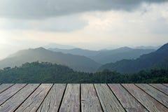 O assoalho de madeira com os montes da montanha enevoada ajardina o fundo Foto de Stock