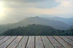 O assoalho de madeira com os montes da montanha enevoada ajardina o fundo Imagem de Stock Royalty Free