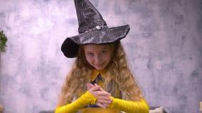 O astrólogo manhoso da bruxa fricciona suas mãos que olham avidamente na câmera Traje branco adolescente novo do Dia das Bruxas d video estoque