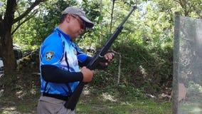 O atirador é treinado na carga no cartucho da bala do rifle filme
