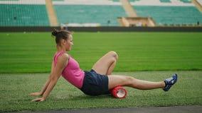 O atleta adolescente da menina usa um rolo da espuma da massagem filme