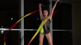 O atleta atrativo bonito magro da menina no roupa de banho colorido brilhante executa elementos da ginástica rítmica com a fita filme