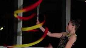 O atleta atrativo bonito magro da menina no roupa de banho colorido brilhante executa elementos da ginástica rítmica com a fita vídeos de arquivo