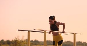 O atleta bonito da mulher no por do sol executa flexões de braço em uma barra horizontal paralela filme