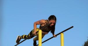 O atleta bonito da mulher no por do sol executa flexões de braço em uma barra horizontal paralela video estoque