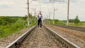 O atleta corre ao longo dos trilhos railway vídeos de arquivo