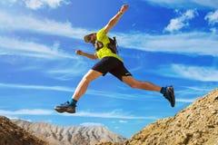 O atleta corre fora de estrada Saltos sobre uma ravina Corredor da fuga no deserto fotografia de stock royalty free