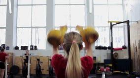 O atleta da jovem mulher executa um impulso longo do ciclo com o kettlebell Menina no gym que faz exercícios da aptidão e dos esp filme