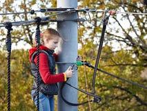 O atleta da menina corre um curso de obstáculo no parque de escalada Imagens de Stock Royalty Free