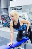 O atleta da menina executa um exercício com os pesos no gym Foto vertical imagem de stock