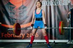 O atleta da mulher executa o barbell bem sucedido do deadlift Foto de Stock