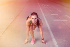 O atleta da mulher no grupo pronto vai posição para começar correr Foto de Stock Royalty Free
