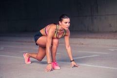O atleta da mulher no grupo pronto vai posição para começar correr Imagem de Stock