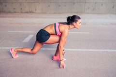 O atleta da mulher no grupo pronto vai posição para começar correr Foto de Stock