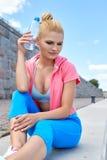O atleta da mulher toma uma ruptura, ela água potável foto de stock royalty free