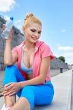 O atleta da mulher toma uma ruptura, ela água potável imagens de stock royalty free