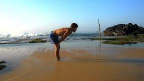 O atleta desportivo está no Sandy Beach molhado com mãos em joelhos video estoque
