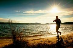 O atleta do homem que verifica o tempo durante o exercício corre o exercício fora na praia do oceano na manhã fria ensolarada Imagens de Stock Royalty Free
