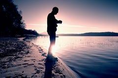 O atleta do homem que verifica o tempo durante o exercício corre o exercício fora na praia do oceano na manhã fria ensolarada Cor Imagem de Stock