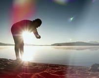 O atleta do homem que verifica o tempo durante o exercício corre o exercício na praia do oceano na manhã ensolarada Imagens de Stock Royalty Free
