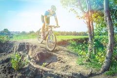 O atleta em um Mountain bike monta ao longo da estrada de terra Fotografia de Stock Royalty Free