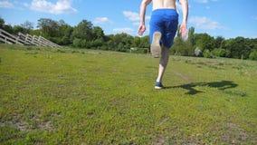 O atleta está agachando-se na linha de partida antes de uma raça e começa a corrida Homem novo no começo da sprint Parte traseira filme