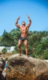 O atleta está em uma rocha pelo mar Fotografia de Stock Royalty Free
