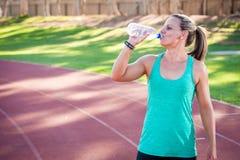 O atleta fêmea bebe de uma garrafa da água Fotografia de Stock