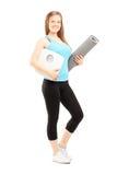 O atleta fêmea de sorriso que guarda um peso escala e esteira Foto de Stock Royalty Free