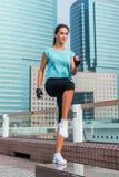 O atleta fêmea novo concentrado que executa a etapa do salto levanta o exercício no banco na rua da cidade foto de stock royalty free