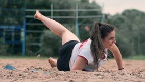 O atleta fêmea novo mergulha na areia e salvar um ponto durante o fósforo do voleibol de praia A menina caucasiano alegre salta vídeos de arquivo