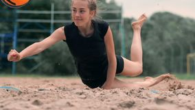 O atleta fêmea novo mergulha na areia e salvar um ponto durante o fósforo do voleibol de praia A menina caucasiano alegre salta filme