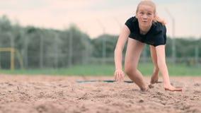 O atleta fêmea novo mergulha na areia e salvar um ponto durante o fósforo do voleibol de praia A menina caucasiano alegre salta video estoque