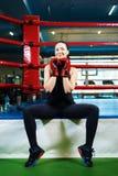 O atleta feliz da menina senta-se em um anel de encaixotamento mulher bonita que sorri e que guarda as mãos em luvas de encaixota imagem de stock