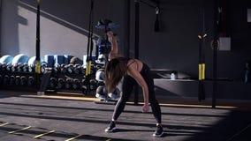 O atleta magro novo bonito da mulher em um sportsuit preto faz as inclinações - aquecer antes de treinar Opinião dianteira uma me video estoque